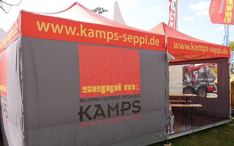 2 orange-graue Faltpavillons von Kamps Seppi, welche auf einer Messe miteinander verbunden wurden.