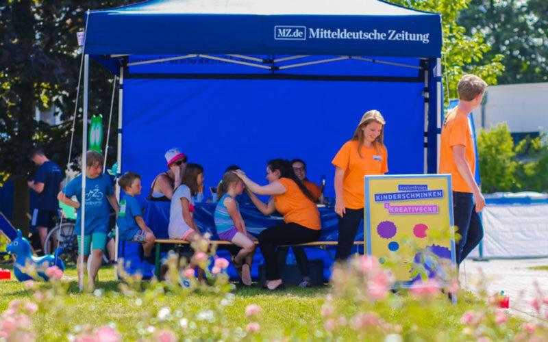 Kinderschminkecke bei der MZ Radpartie unter einem Faltpavillon mit dem Aufdruck