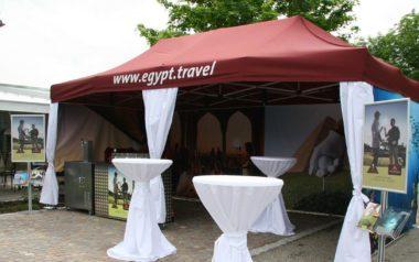 Eleganter Faltpavillon in bordeaux rot mit weißen Eckvorhängen für Egypt Travel.
