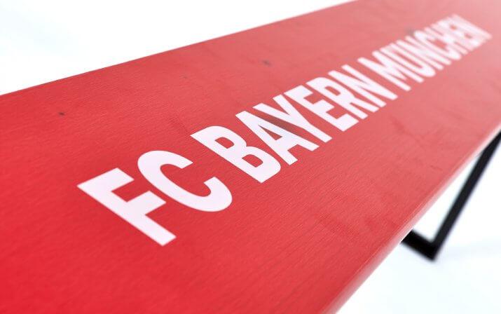 Eine Detailaufnahme des aufgedruckten FC Bayern München Schriftzugs auf der Bierbank der klassischen Bierzeltgarnitur im FCB-Design.