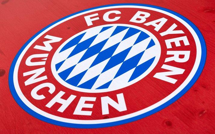 Eine Detailaufnahme des aufgedruckten FC Bayern München Logos auf dem Biertisch der klassischen Bierzeltgarnitur im FCB-Design.