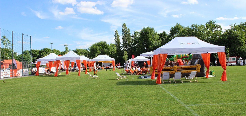 Weiße Faltpavillons mit orangen Vorhängen auf dem grünen Rasen beim ING-DiBa Partnercup 2017