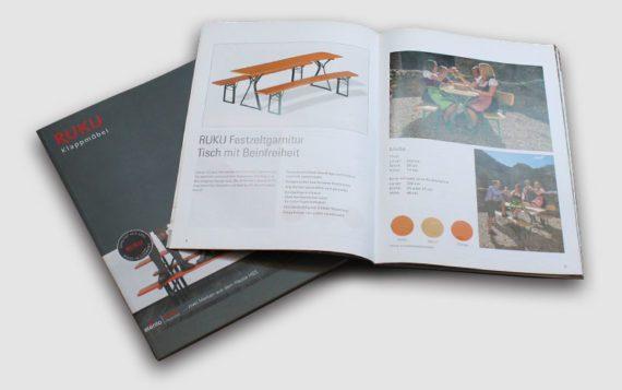 Der Katalog von den RUKU Klappmöbeln mit der Seite der Bierzeltgarnituren aufgeschlagen.