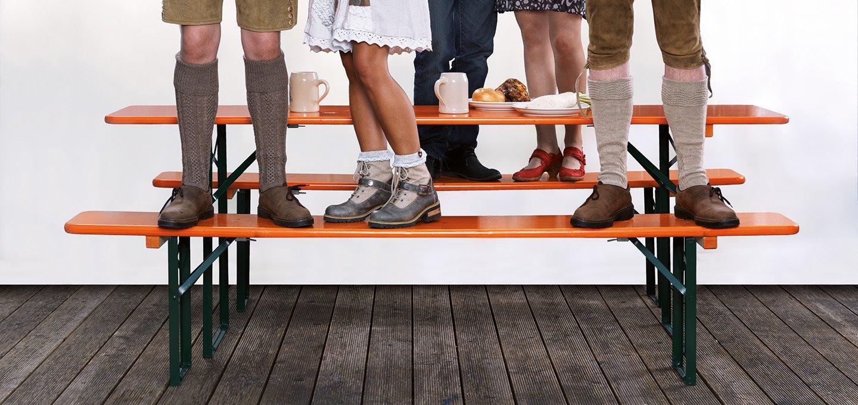 Personen die mit Dirndl und Lederhosen auf einer Bierzeltgarnitur stehen. Man sieht nur die Füße.