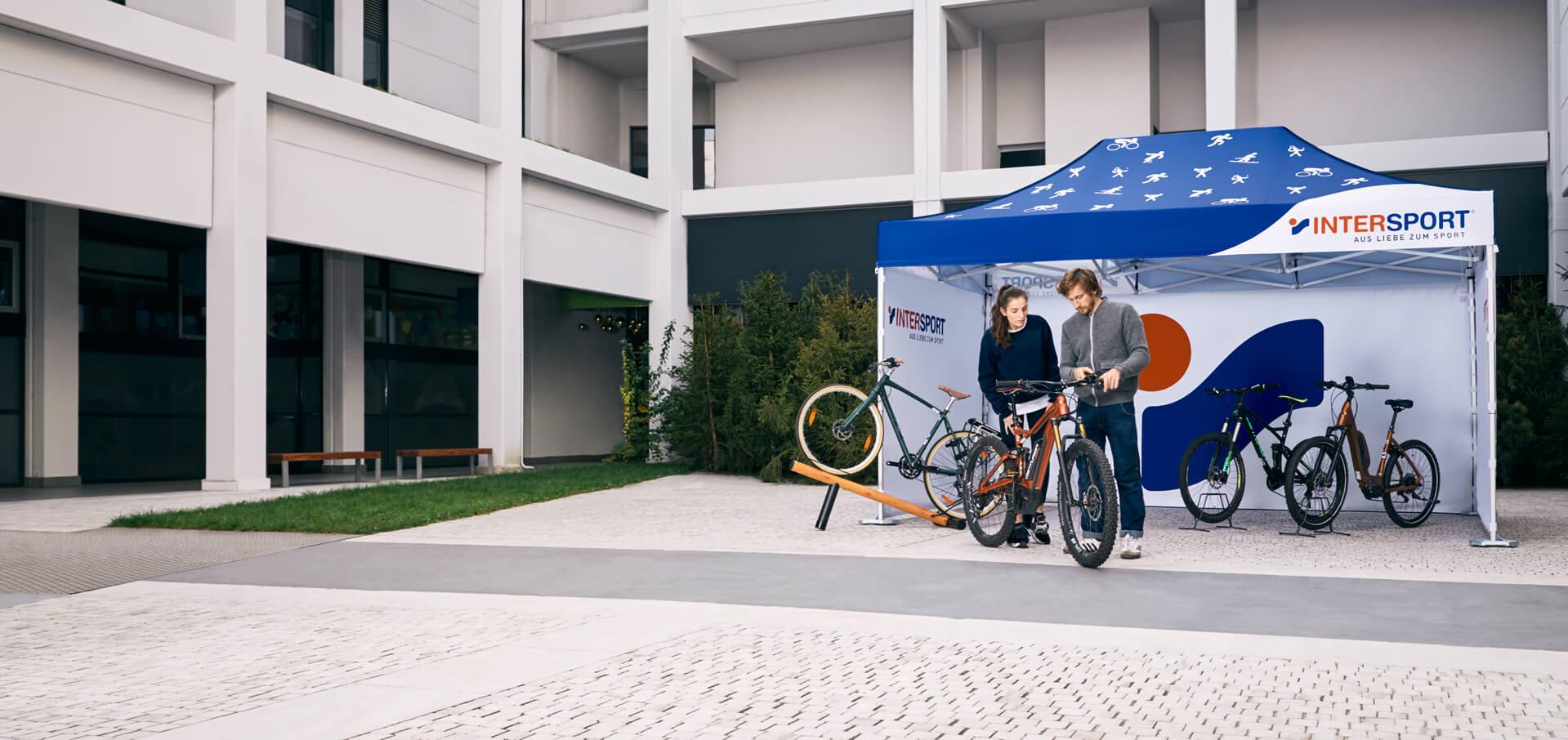 Bedruckter Faltpavillon von Intersport. Der gesamte Faltpavillon ist in den Intersport-Farben bedruckt und es werden damit Fahrräder verkauft. Vor dem Faltpavillon wird ein Verkaufsgespräch geführt.