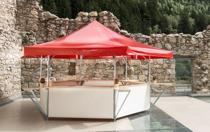 Roter Bierstand von RUKU mit Thekenverlängerung vor einer Steinmauer.