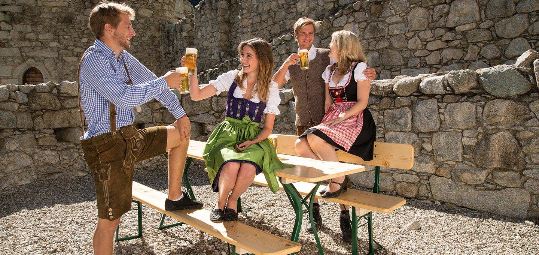 Biertischgarnitur mit Lehne und dem Tisch mit extra Beinfreiheit. 2 Frauen und 2 Männer stoßen in Dirndl und Lederhosen mit einem Bier an.