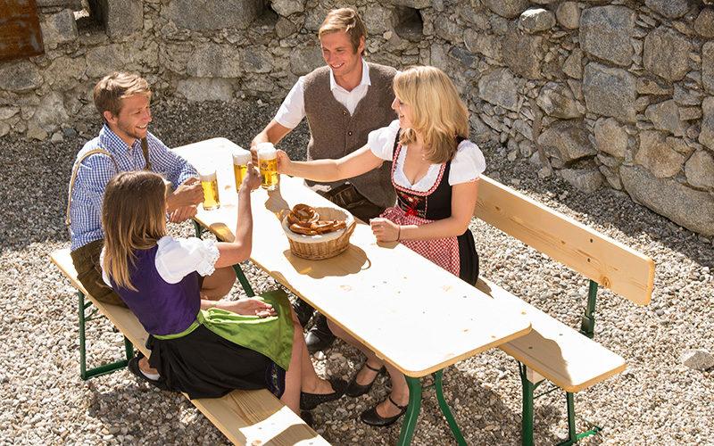 2 Männer und 2 Frauen sitzen bequem auf einer Biertischgarnitur mit Rückenlehne und stoßen mit einem Bier an.