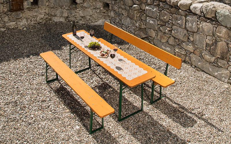 Biertischgarnitur mit einer Bank mit Rückenlehne und einer Bank ohne Lehne. Der Tisch ist mit Speisen gedeckt.