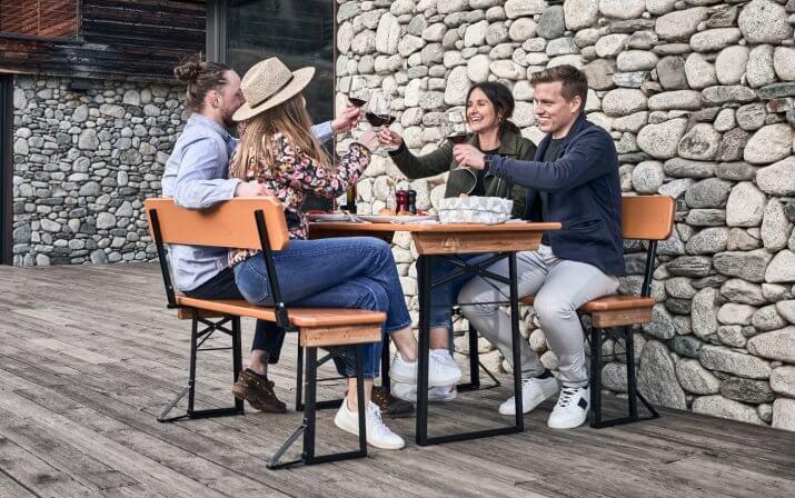 Vier Personen essen zu Mittag auf einer kurzen Bierzeltgarnitur mit Lehne auf der Terrasse.