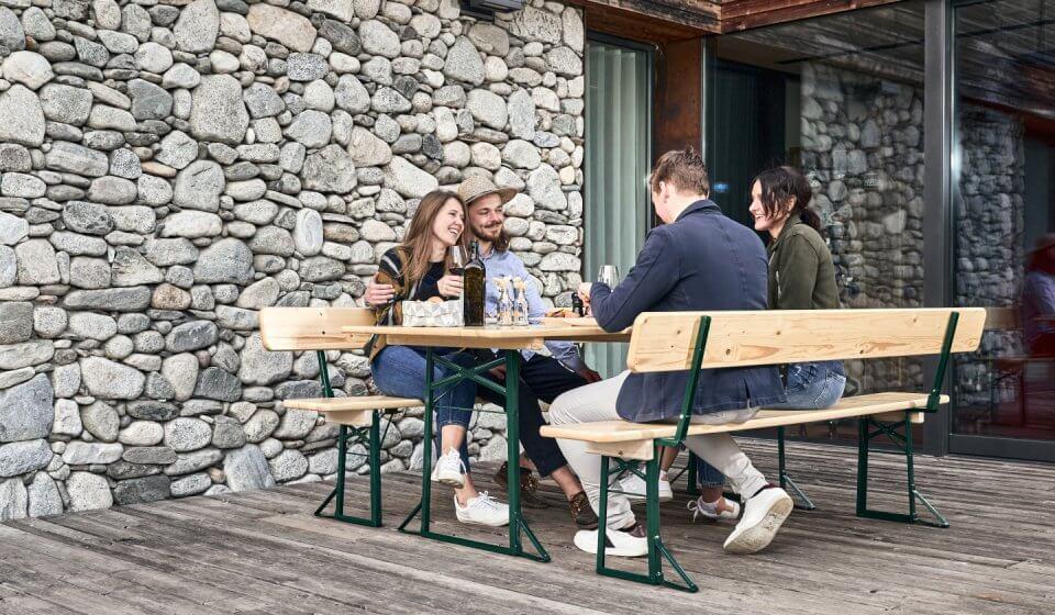 Vier Personen essen zu Mittag auf einer Bierzeltgarnitur mit Lehne auf der Terrasse.