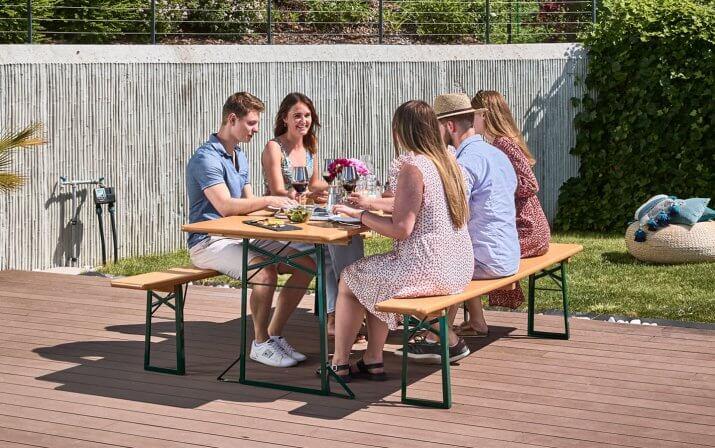 Fünf Personen sitzen am gedeckten Tisch der Bierzeltgarnitur und essen und trinken Wein.