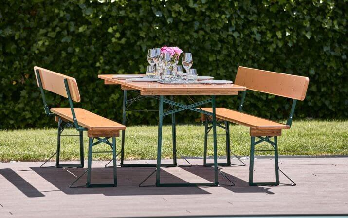 Der Tisch einer breiten Bierzeltgarnitur ist gedeckt und steht zusammen mit zwei Bänken mit Lehne auf der Terrasse vor einer Wiese.