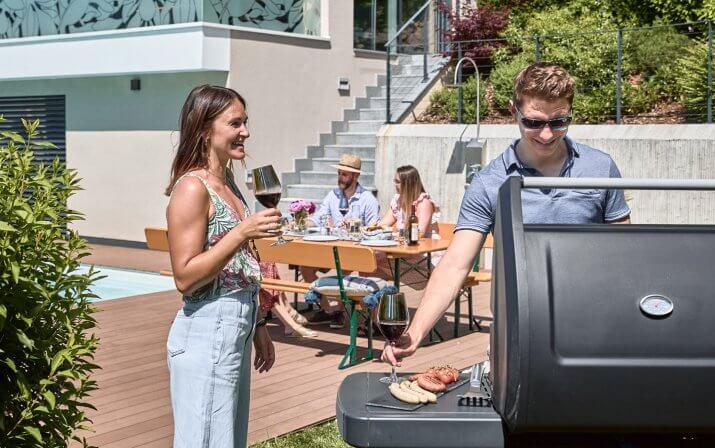 Zwei Personen stehen vor einem Grill und unterhalten sich während sie Wein trinken. Im Hintergrund sind drei Personen, die bei einem gedeckten Tisch sitzen und sich unterhalten. Sie lehnen sich an der Lehne an.