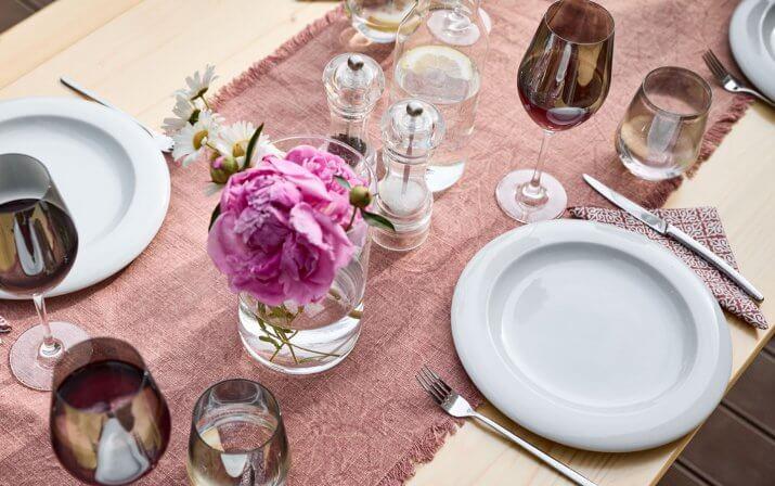Man sieht eine Nahaufnahme eines Tisches von einer Biertischgarnitur, auf dem pinke Blumen und Teller, Gabeln und Gläser stehen.