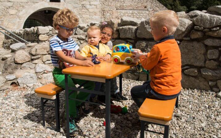 Mehrere Kleinkinder spielen sitzend auf einer kleinen, klappbaren Bierzeltgarntiur.