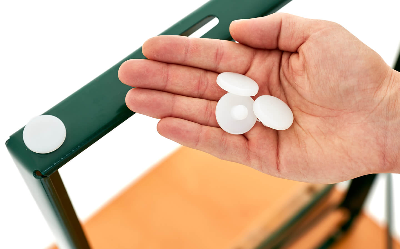 Ein Kunststoffgleiter ist an der Unterseite des Untergestelles der Bierzeltgarnitur angebracht, um empfindliche Böden im Innern vor Kratzern zu schützen. In der Hand einer Person liegen weitere drei Kunststoffgleiter.