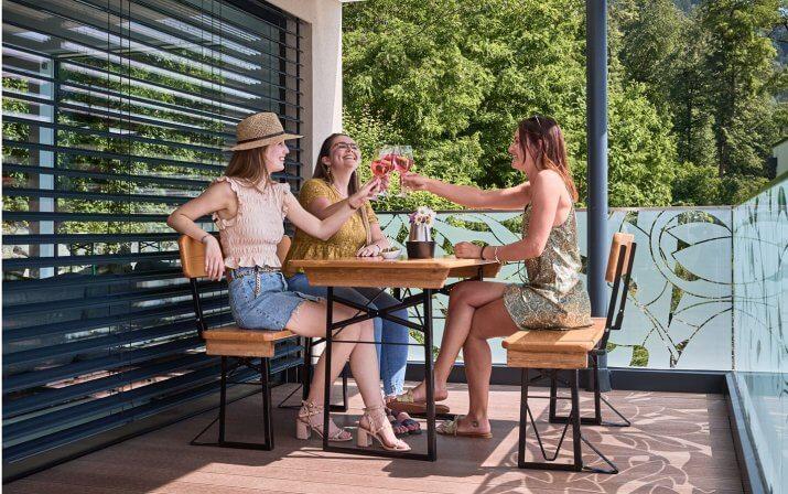 Drei Frauen sitzen auf einer Bierzeltgarnitr mit Lehne und stoßen mit ihren Gläsern an. Die Garnitur steht auf der Terrasse eines Hauses, das man im Hintergrund sehen kann.