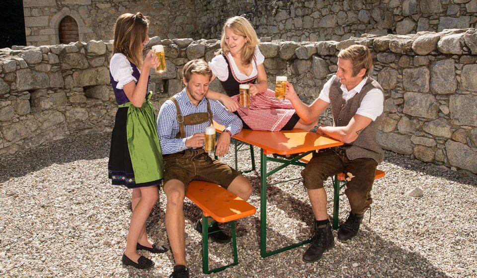 4 feiernde Personen in Tracht, darunter 2 Frauen mit Dirndl und 2 Männer mit Lederhosen, sitzen auf der Bierzeltgarnitur und haben allesamt ein Bierglas in der Hand.