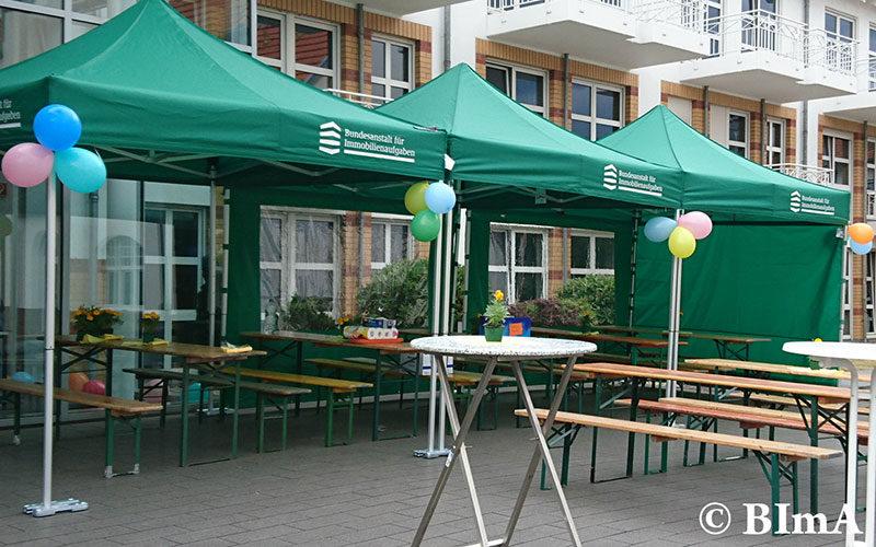 Grüne Faltpavillons miteinander verbunden und mit verschiedenen Seitenwänden ausgestattet.