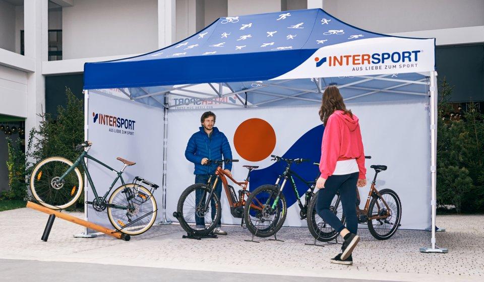 Sowohl das Dach als auch die drei geschlossenen Seitenwände des Faltpavillons sind in den Farben und mit dem Logo von Intersport bedruckt. Der Verkäufer präsentiert seiner Kundin verschiedene Fahrräder und Mountainbikes unter seinem personalisierten Intersport-Verkaufsstand.