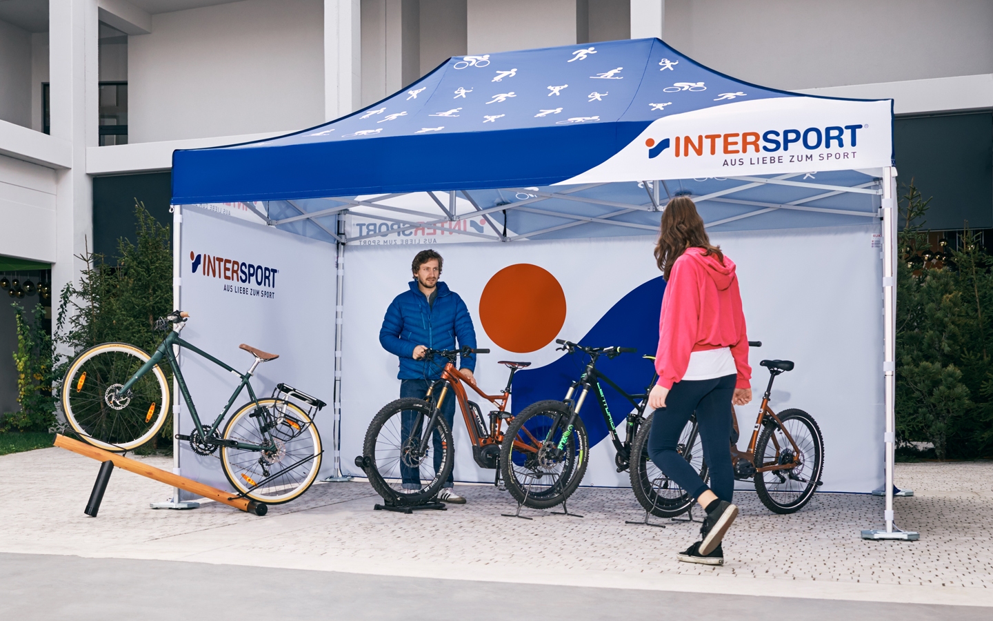 Both the roof and the three closed side walls of the canopy tent are printed in the colors and with the logo of Intersport. The salesman presents various bicycles as well as mountain bikes under his personalised Intersport sales stand.