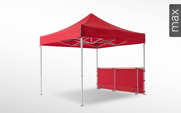 Eine rote halbhohe Seitenwand mit Theke ist an einem 3x3m großen Faltpavillon der Linie max angebracht (mit Klettverschlusslaschen). Das Label am rechten Rand zeigt, dass der Faltpavillon in der Linie max erhältlich ist.
