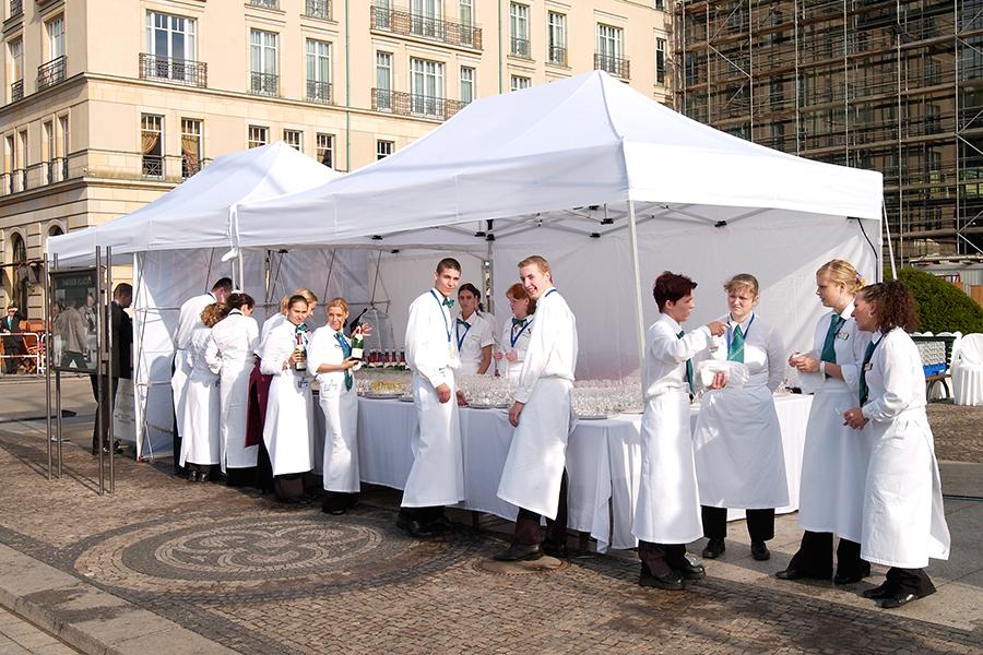 Weiße Faltpavillons im Einsatz bei einem Cateringunternehmen mit den Mitarbeitern davor.