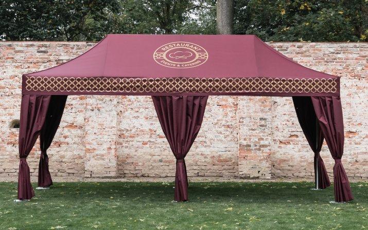 Ein 6x3 m großer Faltpavillon in Bordeaux-Rot mit Eckvorhängen und bedruckter Blende und rundem Logo des Restaurants auf dem Dach steht auf der Wiese vor einer Mauer. Die Bedruckung ist in Gold.