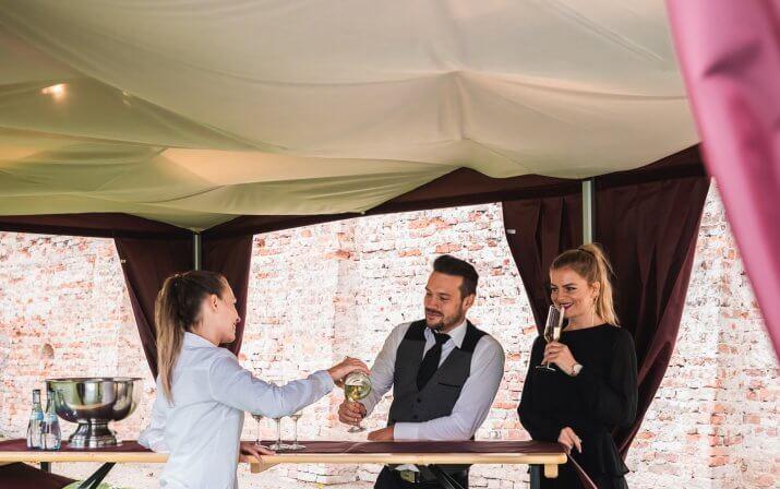 Die weibliche Bedienung schenkt den beiden elegant gekleideten Gästen am Stehtisch unter dem Gastronomiezelt mit Eckvorhängen, Himmel und Beleuchtung Sekt ein.