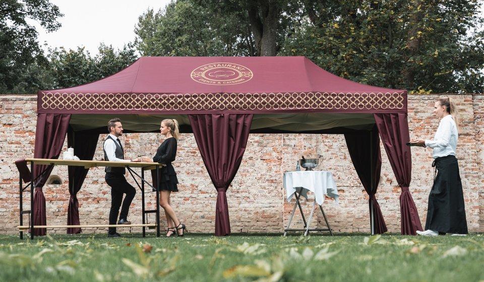 Zwei elegant gekleidete Gäste warten an einem Stehtisch vor dem Bordeaux-Roten Faltpavillon mit Eckvorhängen auf die Kellnerin, die ihre Drinks serviert.