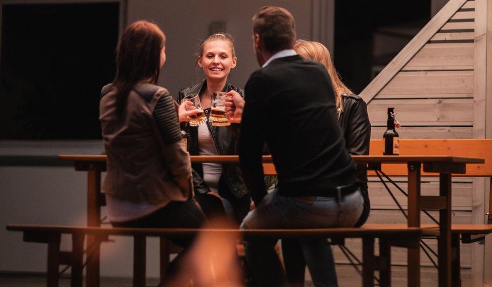 Vier Personen, darunter 3 Frauen und 1 Mann, stoßen mit Bier auf der klappbaren Designgarnitur