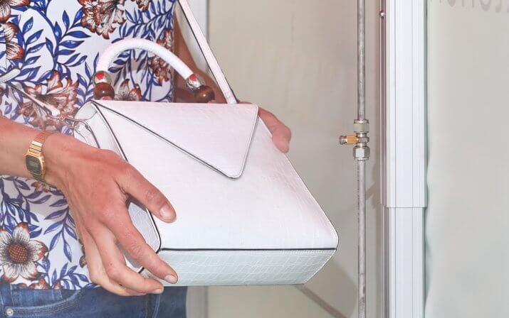 Eine Frau hat die Desinfektionsschleuse betreten und desinfiziert ihre Handtasche, indem Sie diese vor die Düsen hält.
