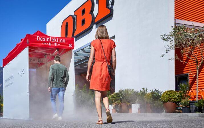 2 Personen laufen hintereinander in die Desinfektionsschleuse vor dem Obi-Eingang.