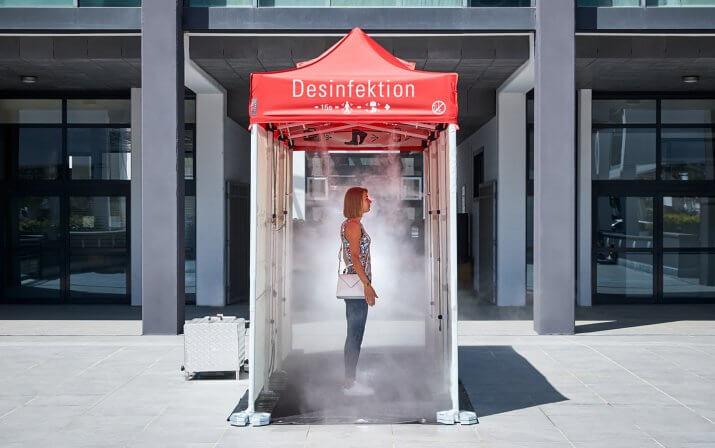 Eine Frau hat die Desinfektionsschleuse betreten, sich 90° gedreht und steht mitten im Nebel.