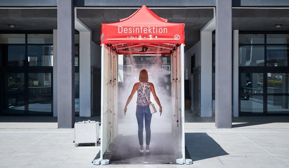Eine Frau hat die Desinfektionsschleuse betreten und steht mitten im Nebel.