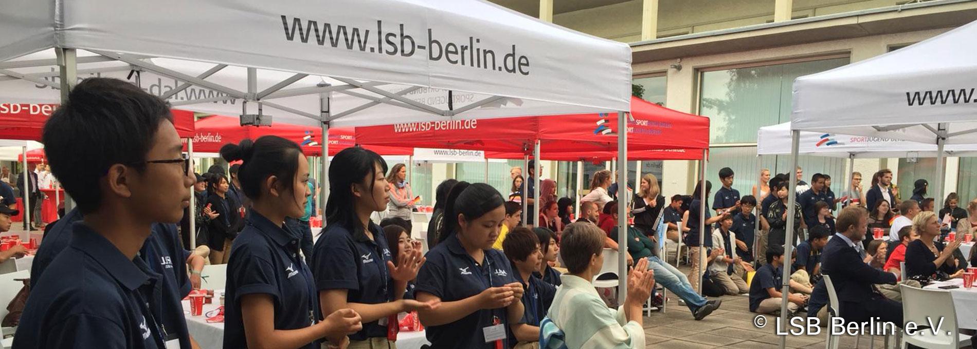 """Japanishche Sportjugend unter einem weißen Faltpavillon mit dem Aufdruck """"www.lsb-berlin.de""""."""