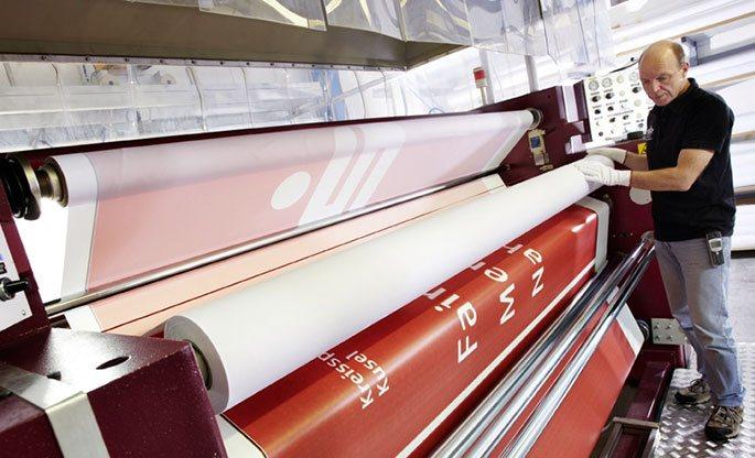 Mitarbeiter beim Drucken einer Seitenwand für den Faltpavillon im eigenen Grafik-Studio.