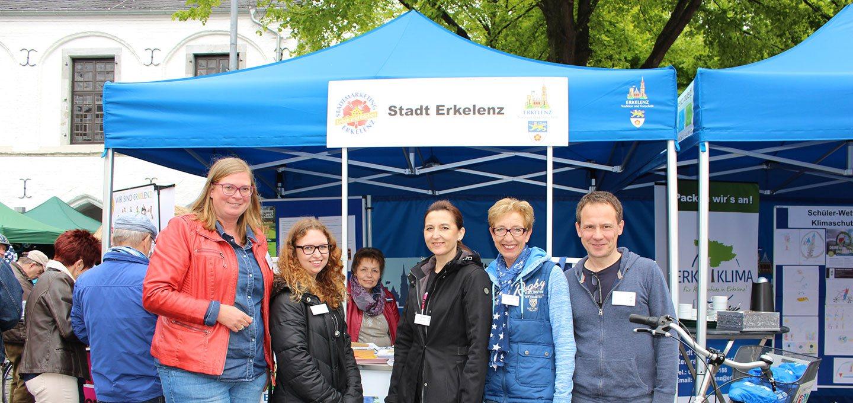 Blauer Faltpavillon der Stadt Erkelenz mit Personen im Vordergrund.