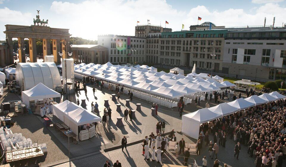 Many white canopy tents at a major event in front of the Brandenburg Gate in Berlin.