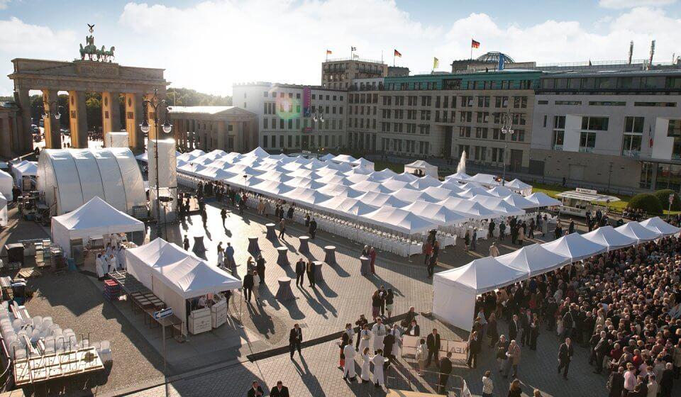 Viele weiße Faltpaviillons bei einem Großevent vor dem Brandenburger Tor in Berlin.