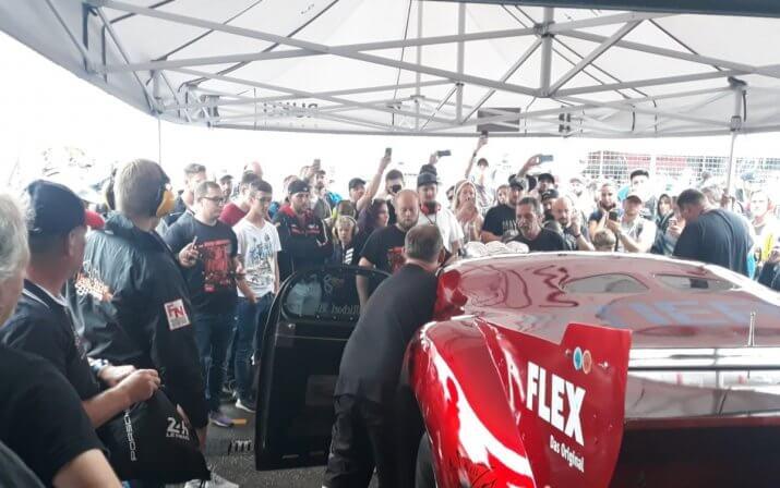 Ein Auto wird unter dem Faltpavillon präsentiert, während die Besucher zu sehen und mit ihren Smartphones aufnehmen.
