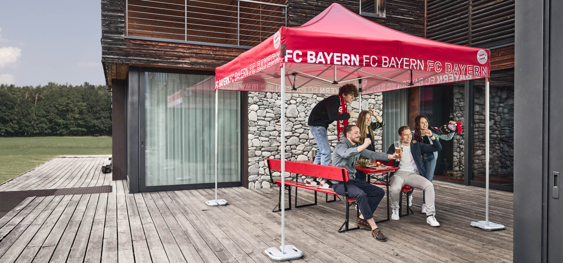 Fünf Personen feuern ihre Lieblings-Fußballmannschaft an - auf einer Bierzeltgarnitur und unter einem Faltpavillon im FC Bayern München Stil.