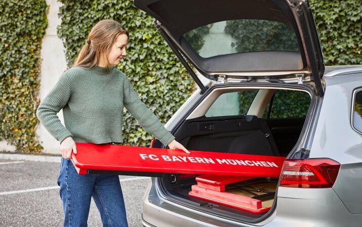 Frau hält eine Bank einer FC Bayern München in der Hand und verstaut diese im Kofferraum ihres Autos. Mit der Länge von 180 cm passt diese perfekt ins Auto.