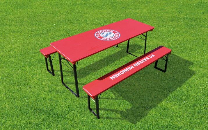 Die klassische Bierzeltgarnitur im FC Bayern München Design auf dem Rasen.