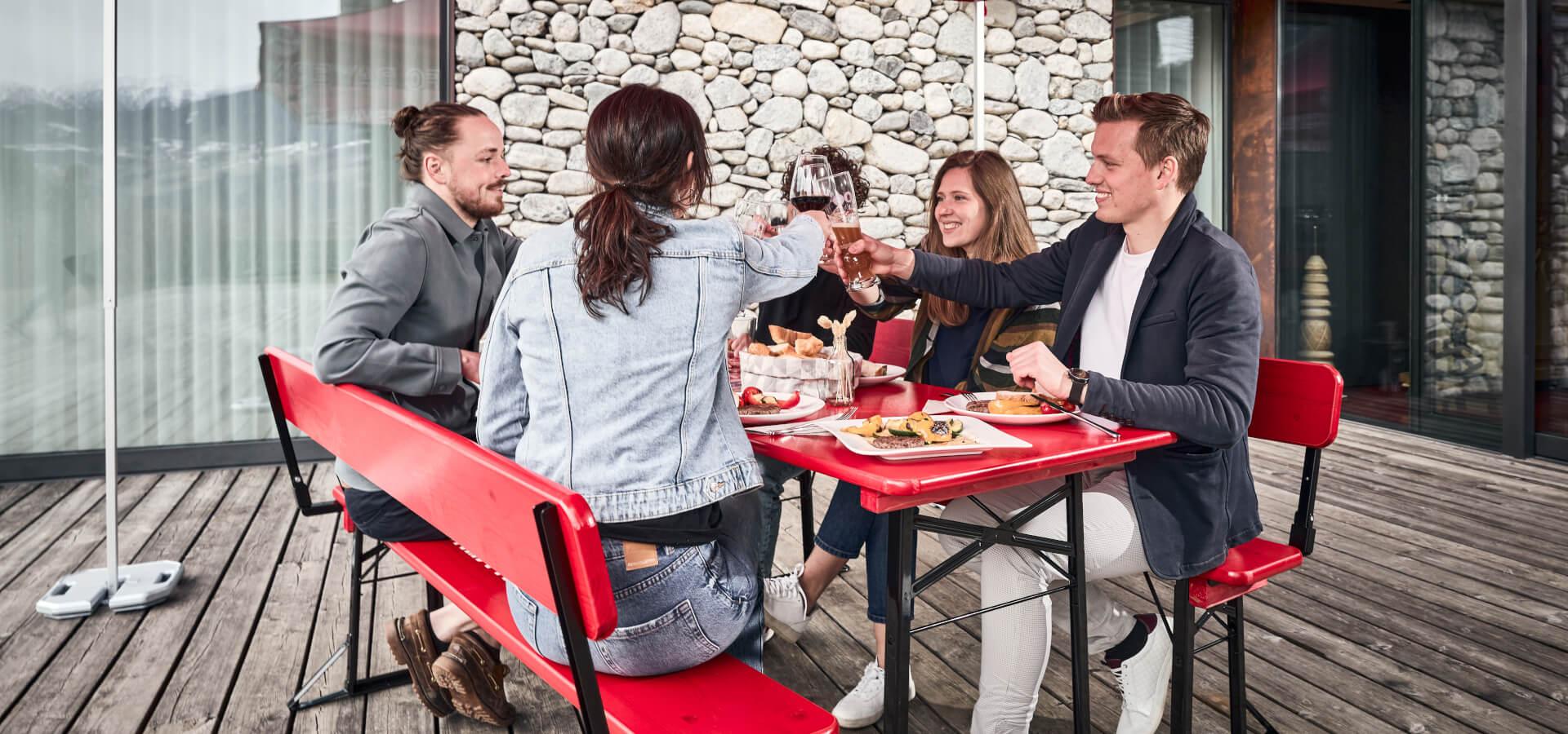 Fünf Personen stoßen beim Essen gemeinsam, auf einer Bierzeltgarnitur und unter einem Faltpavillon im FC Bayern München Stil, an.
