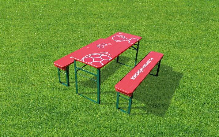 Die kleine Bierzeltgarnitur Bambini im FC Bayern München Design auf dem Rasen.