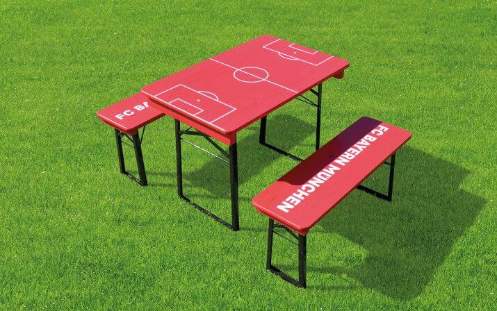 Die kurze Bierzeltgarnitur Shorty im FC Bayern München Design auf dem Rasen.
