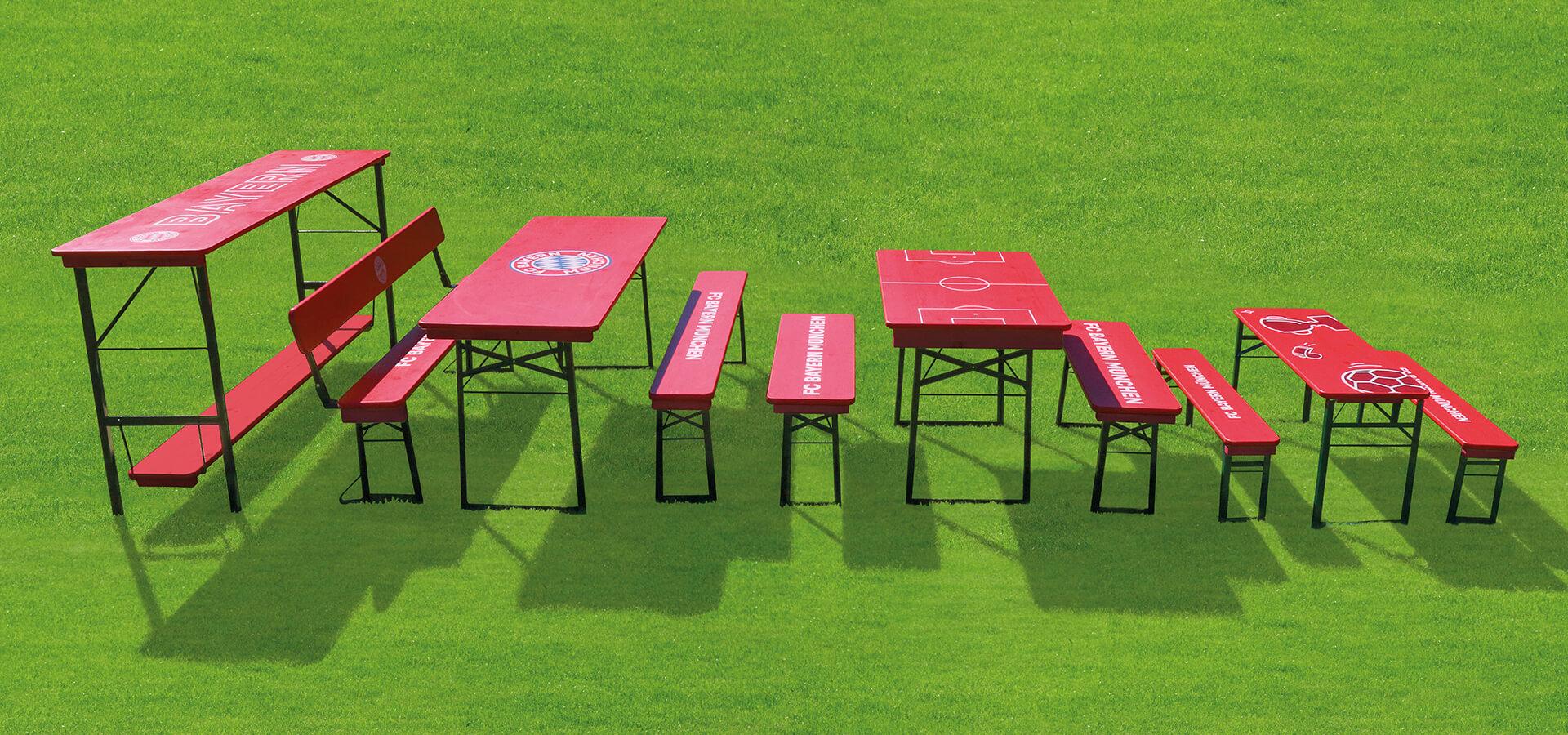 Die FC Bayern München Garnituren stehen auf dem Rasen. Von links nach rechts, der FCB Stehtisch, die klassische Bierzeltgarnitur, wobei eine Bank mit Lehne bestückt ist, die FCB Shorty Garnitur und die kleine Bierzeltgarnitur Bambini.
