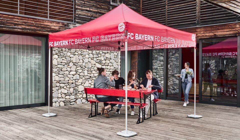 Vier Personen essen auf einer Bierzeltgarnitur und unter einem Faltpavillon im FC Bayern München Look zu Mittag. Eine Frau serviert das Essen.